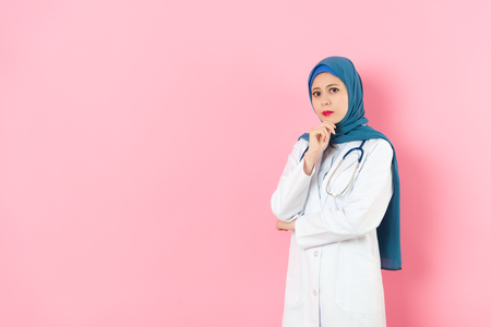 attractive pretty female muslim doctor looking at camera when she standing in pink background thinking medical work solution.