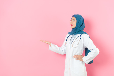 smiling elegant muslim female hospital doctor looking at empty area and standing in pink background making presentation posture. Stockfoto