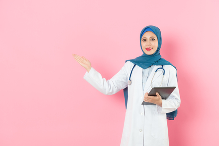 professional young muslim female doctor carrying mobile pad computer work and showing empty area face to camera isolated on pink background.
