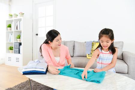 Bastante joven ama de casa haciendo tareas de limpieza en la sala de estar y hermosa hija pequeña belleza ayudándola a doblar la ropa de la familia.