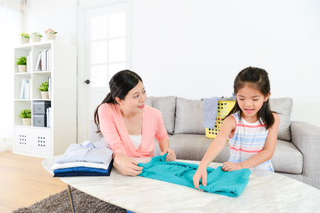 pretty young housewife doing housekeeping work in living room and lovely beauty little daughter helping her to fold family clothing.