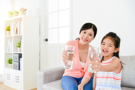 cheerful lovely little girl kid children with mother showing healthy water face to camera. Standard-Bild