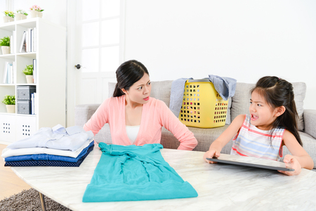 Attractive young little daughter feeling afraid when mother folding clothing at home finding she using mobile pad computer playing game. Stock Photo