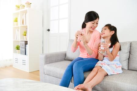 Attraktive Schönheit kleine kleine Kinder Kinder mit Mutter sitzen auf Sofa Couch entspannen und halten Wasser einander Standard-Bild