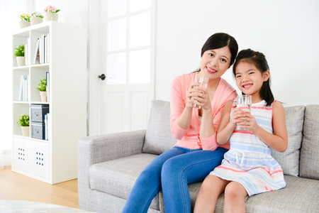 smiling young woman and happy cute little girl sitting on sofa couch and holding glass cup with health drink water looking at camera. Фото со стока - 96063773