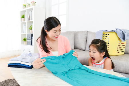 elegant beauty housewife folding family clothing in living room and her little daughter feeling surprised.