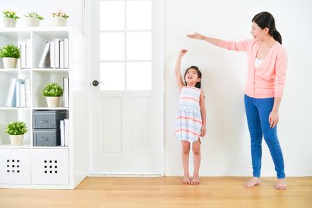 hübsche attraktive Mutter mit niedlichen kleinen Tochter messen Wachstumsrekord, wenn sie im Holzboden mit weißem Hintergrund zusammen stehen.