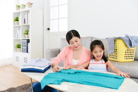 happy young little daughter helping mother folding family clothing at home and learning how to organize tidy clothes by herself. Banque d'images