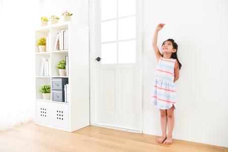 Hermosa joven niña niño niños de pie en el piso de madera con fondo blanco y mirando arriba usando la mano midiendo su altura.