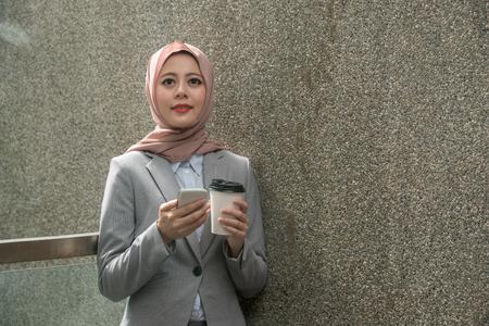 smiling professional muslim female office worker taking break in outside.