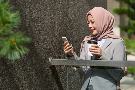 elegant attractive female muslim office worker using mobile smartphone checking personal work e-mail and standing in company outside relaxing.