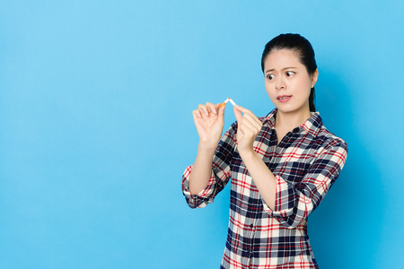 angry young woman bending cigarette showing quit smoking concept isolated on blue background.