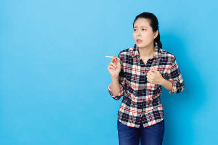 elegant beauty woman standing in blue background smoking and getting short breathing feeling heartache.