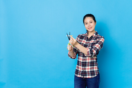 confident pretty woman using scissors tool cutting nicotine cigarette and looking at camera smiling isolated on blue background.