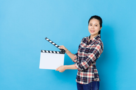 confident young female director using clapperboard tool announcing movie work start isolated on blue background and looking at camera smiling.