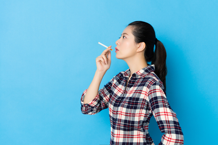 side view photo of pretty elegant female model holding cigarette and making smoking posture isolated on blue wall background.