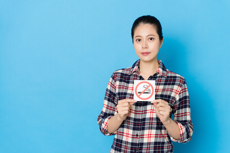 pretty attractive woman showing quitting forbidden smoking cigarette symbol sign face to camera isolated on blue background.