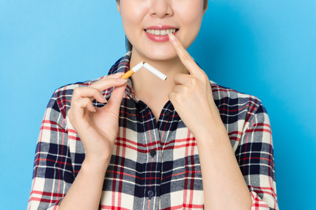 smiling elegant woman pointing personal tooth and holding bend cigarette showing oral cancer sick concept when she standing in blue background.