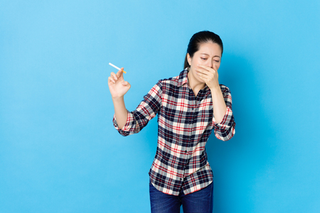 beauty young woman having smoking habit and already getting sick standing in blue background cough.