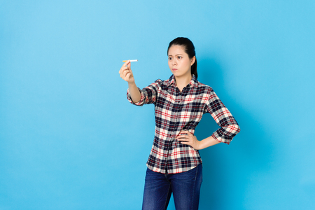 pretty elegant woman looking at cigarette feeling confused and thinking how to quit smoking isolated on blue background.