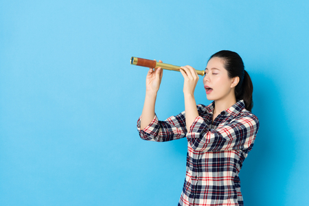 attractive young female teenager standing in blue background and using telescopic telescope looking for distance beautiful view.