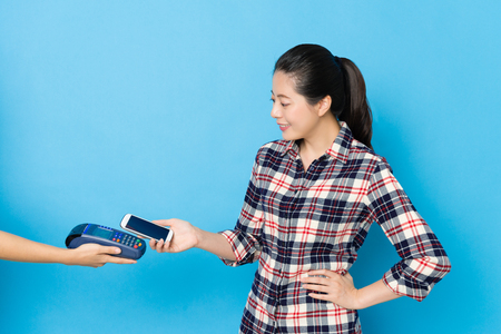 pretty beautiful woman using mobile smar tphone near credit card machine to pay spent bill isolated on blue wall background. Foto de archivo - 96213350