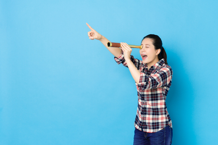 happy beautiful woman pointing distant when she using stretch telescope tool finding goal isolated on blue wall background. Banque d'images