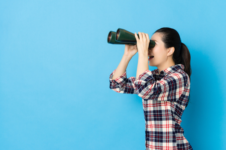 side view photo of happy beauty girl playing telescope feeling funny isolated on blue background.