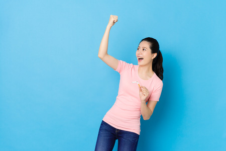 cheerful pretty woman successful quit smoking and standing in blue background celebrating.