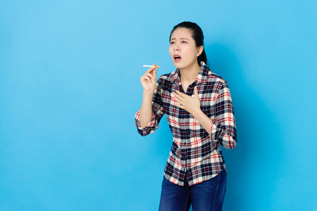 attractive young girl smoking long time feeling painful and cough when she holding cigarette standing in blue background.