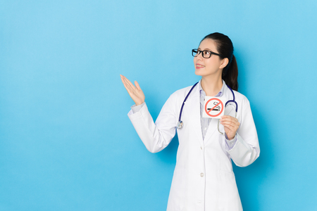 professional pretty female hospital doctor making presenting posture and showing forbidden smoking symbol sign isolated on blue background.