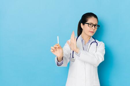 mooie jonge vrouwelijke ziekenhuis arts weigerde sigaret en tonen stoppen met roken concept geïsoleerd op blauwe muur achtergrond.