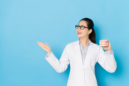 smiling elegant female hospital doctor showing dental teeth mold and making presentation posture isolated on blue background.
