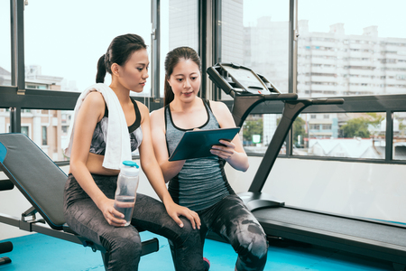 personal Asian fitness instructor is explaining the recording on the clipboard to her student who would like to lose weight after the workout.