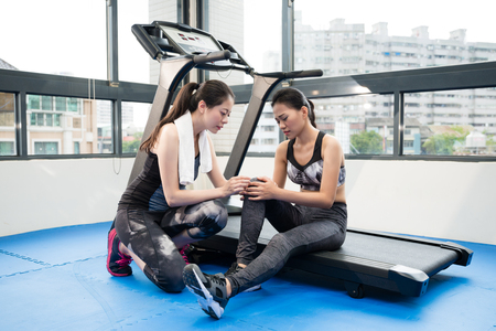 women who get injured on her knee when running on the treadmill machine and sitting down, her instructor is checking for her.