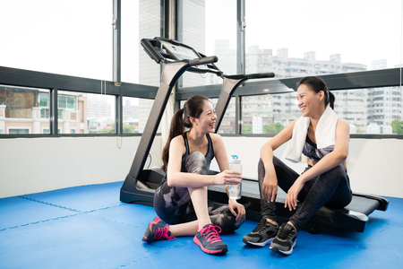 two beautiful Asian girls sitting on the treadmill and drinking water take a break after exercise in the fitness gym.