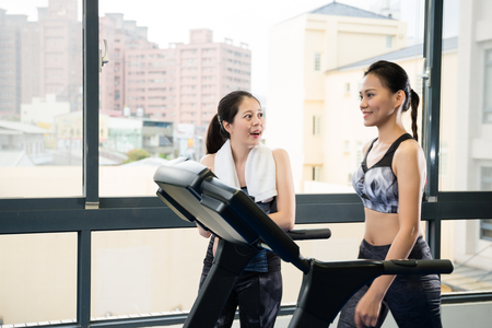 girl meet and talking to her friend who walking on treadmill machine and enjoys the workout together in the gym.