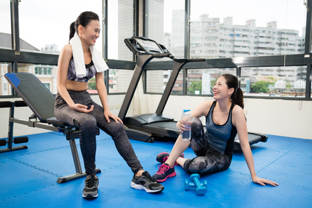 two Asian girls sitting and chatting in the gym floor, drinking water and have a rumor conversation.