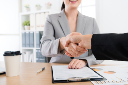 On a side view of two business women make the deal . A closeup picture of thier shaking hands.  Stock Photo