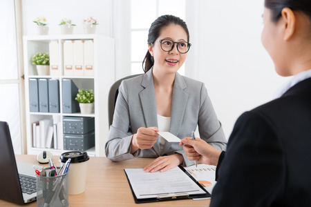 Young asian office lady introduce herself and then give her bussiness card to the boss .