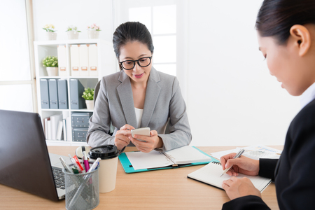 Asian female boss speaking to office lady assistant. Supervisor using smartphone device saying .Assistant write it down using notebooks and pan in the company office. Reklamní fotografie