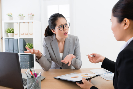 Asian female boss confuse with diagram project and asking the employee blaming office lady workshit with her gesture and mean face . She is unhappy upset question with something.