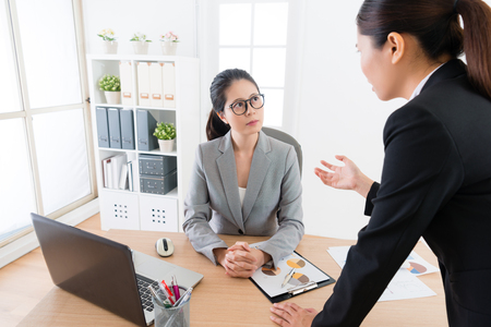 Asian female office lady explanning her project plan to her manager boss and share her viewpoint . Using a workship with a diagram. On above view. Boss focus and concentrating listening to her.