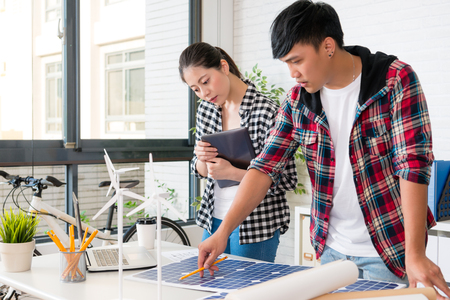 male alternative energy engineer pointing to a solar power panel and discuss with his woman colleague team for the future power in the office