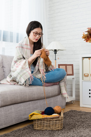 beauty asian woman put the blanket on body and knitting for coming season sitting on sofa in the living room at home in autumn season