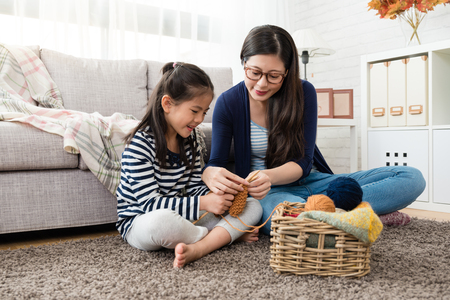 beautiful Asian mom teaches her daughter how to knitting for the autumn sweater for cold season is coming in the living room at home Archivio Fotografico