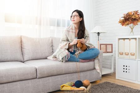 belleza mujer asiática manteniendo el calor poniendo la manta en la parte superior y mirando la vista exterior y tejiendo en el sofá de la sala de estar en casa