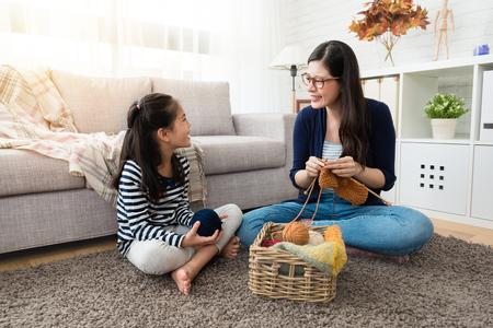 dulces niños asiáticos se quedan con su madre y disfrutan tejiendo juntos sentados en el piso de la sala de estar en casa