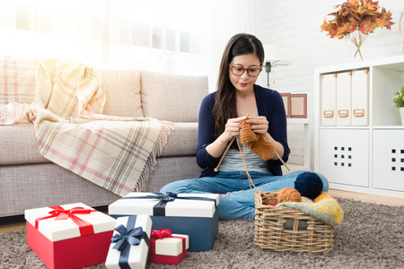 beautiful Asian woman mother knitting making Christmas holiday gift by herself with many presents boxes in the living room at home in the autumn season Stock Photo