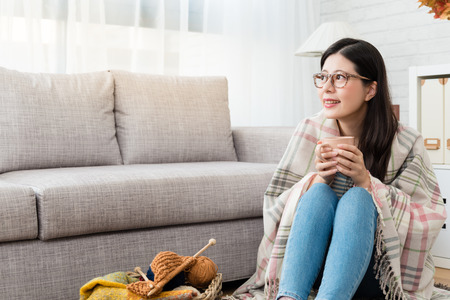 smile Asian woman drinking hot chocolate and keeping warm with the wool blanket and looking outside autumn view and knitting on the floor in the living room at home